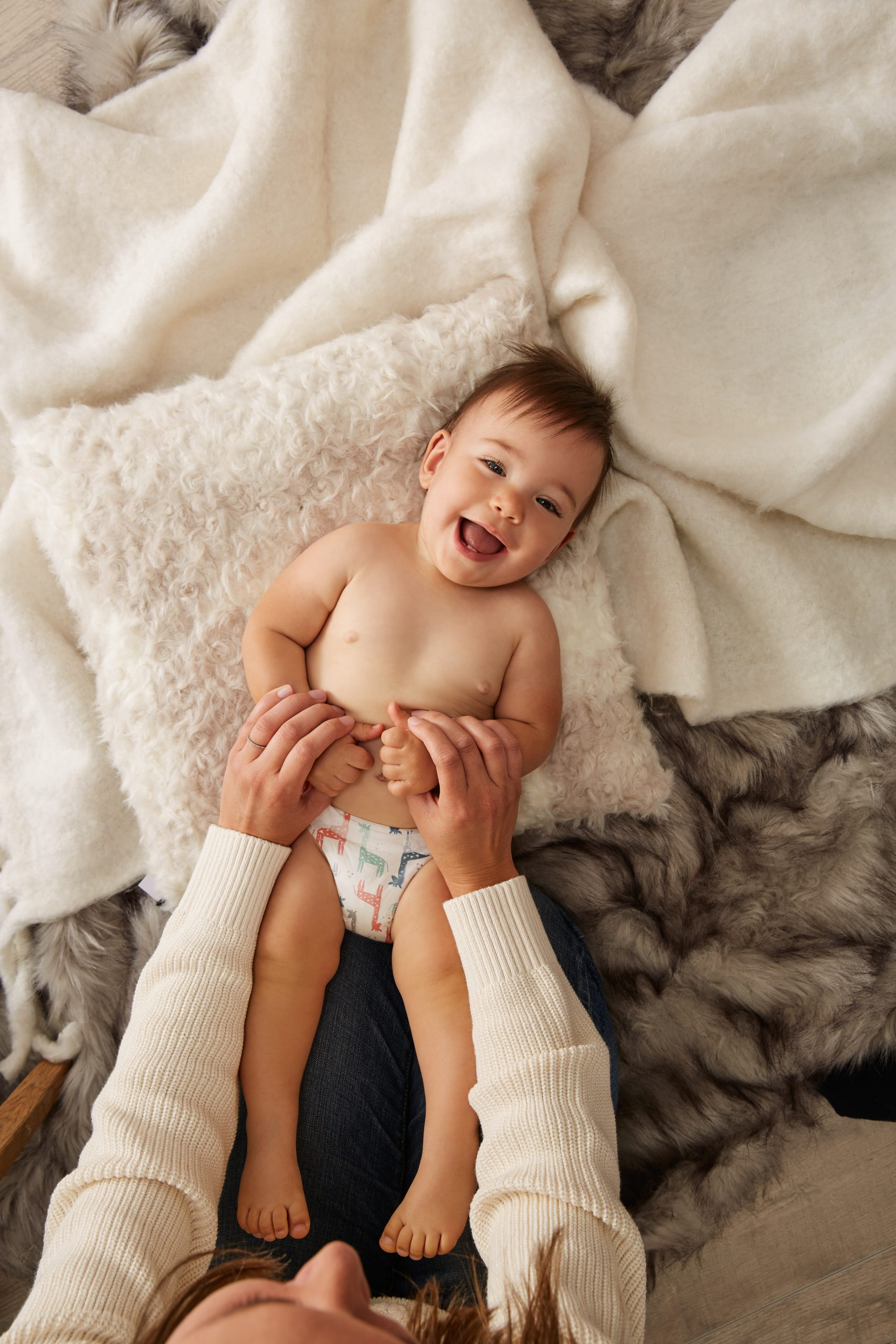 toddler smiling while lying on white pillow